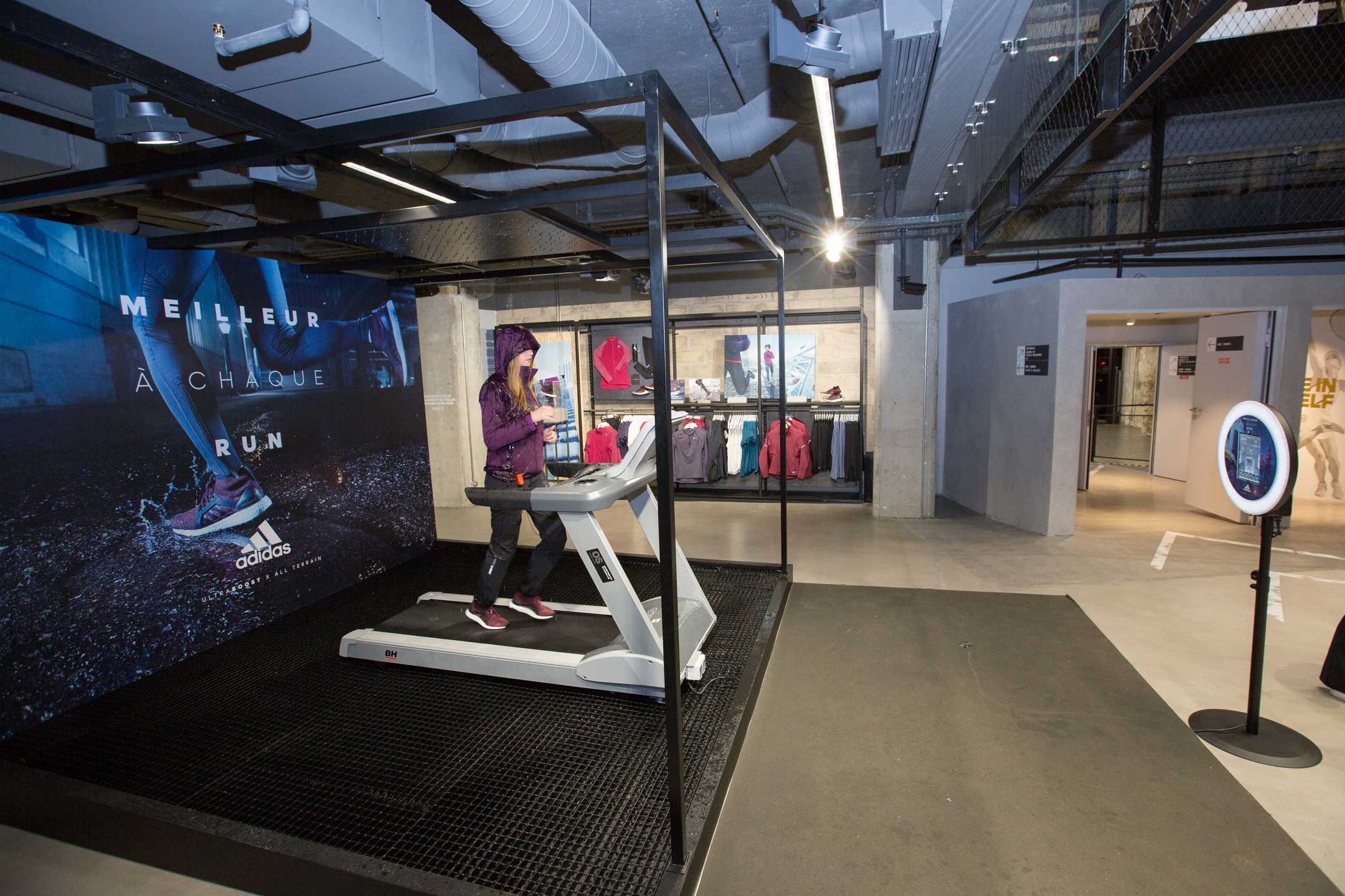 Dans un magasin Adidas, le photobooth de Josepho est installé face à un tapis de course et un photocall. Une femme est sur le tapis de course en train de se prendre en photo avec le photobooth de Josepho personnalisé aux couleurs et logo Adidas.