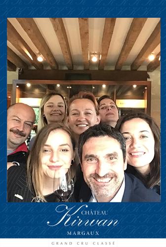 Une photo prise avec le photobooth de Josepho montre un groupe de personnes en train de sourire et se prendre en photo. Le cadre de la photo est personnalisé avec les couleurs et le logo Château Kirwan.