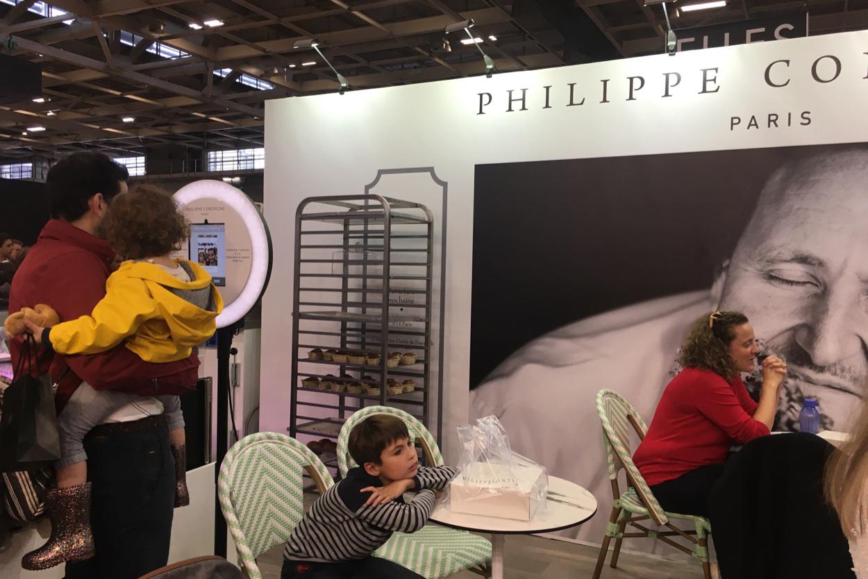 Sur le Salon du Chocolat, un père avec son enfant des les bras se prend en photo avec le photobooth de Josepho qui est personnalisé avec le logo Philippe Conticini.