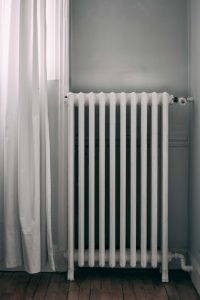 White old fashioned radiator on wooden floor