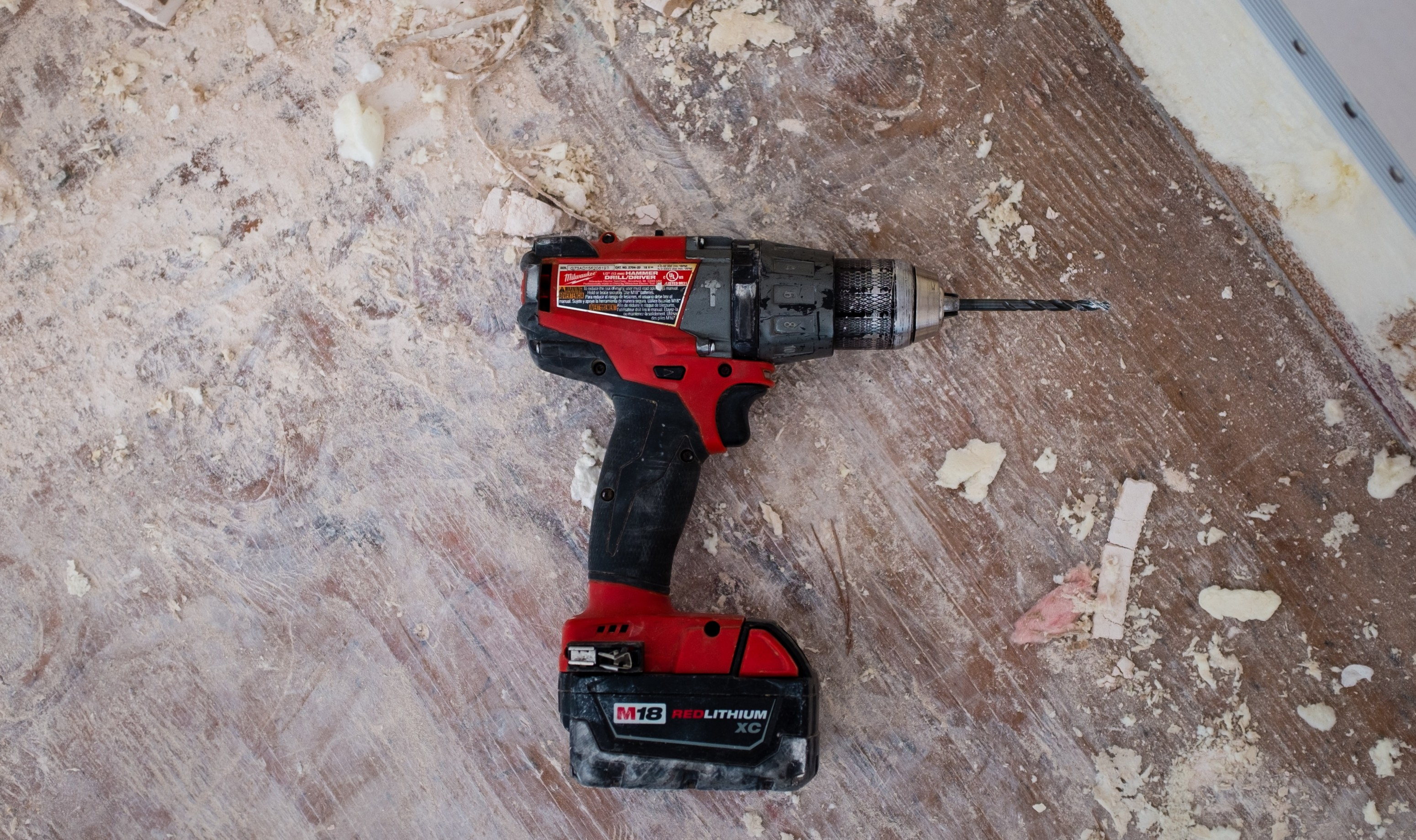 Neon brand drill on a paint covered wooden floor