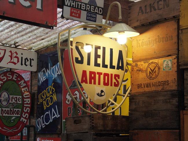 old brand sale signs, focus on yellow Stella Artois sign