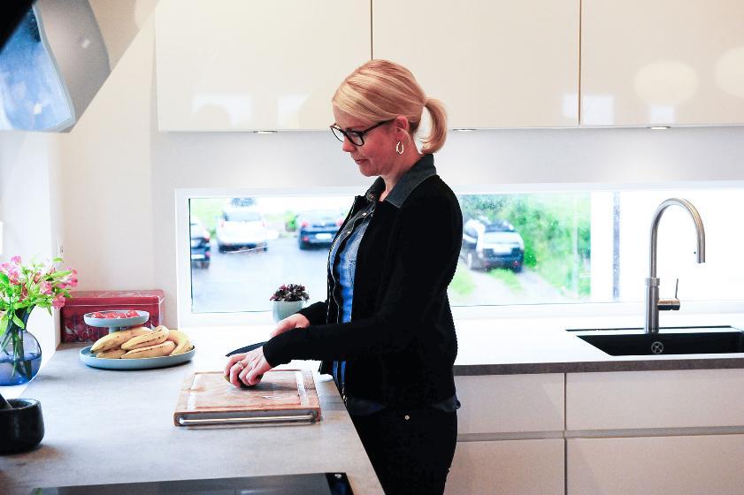 Kvinne ved kjøkkenbenk. Foto.