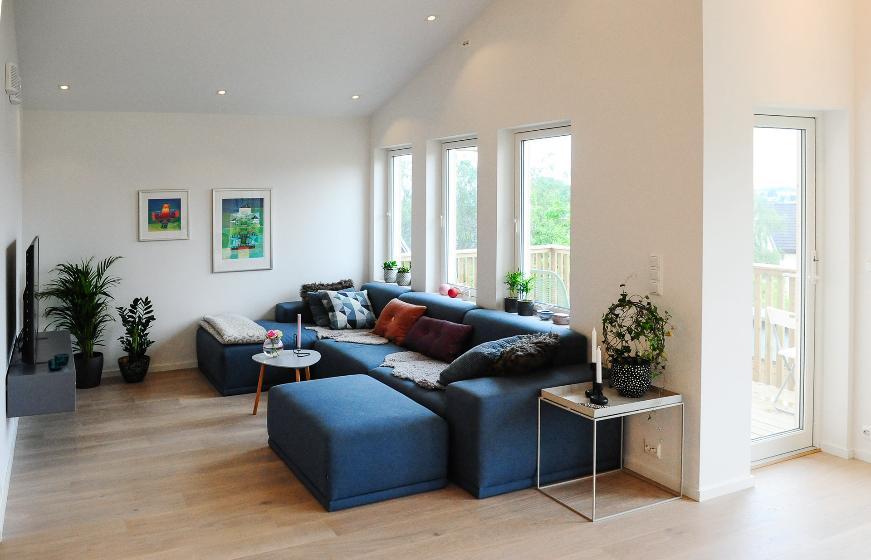 Blå sofa i hvit stue. Foto.