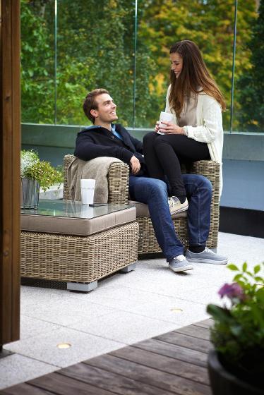 Mann og kvinne sittende i utemøbler Asak Miljøstein. Foto.