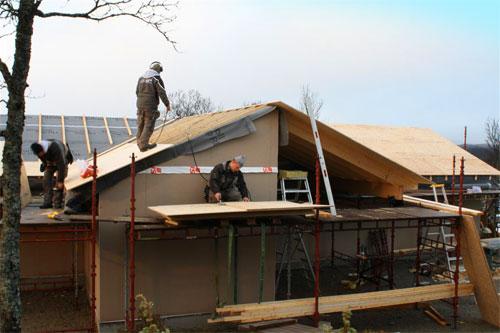 Bilde av tre håndverkere på et tak