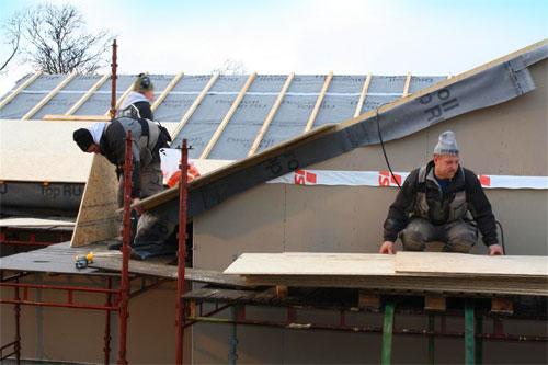 Bilde av to håndverkere på et tak
