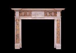 Late Victorian chimneypiece of neo-classical form. In statuary marble with engaged ionic columns inlaid with stop flutes of convent siena and terminating beneath corner blocks carved with lidded urns. The central frieze tablet carved with a reclining female figure and flanked by frieze panels inlaid with flutes of siena with overlaid elliptical rosettes.