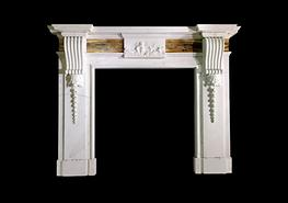 An English chimneypiece in Statuary marble with bookmatched Siena frieze panels each side of a carved centre tablet with strong corbels under the corniced shelf....