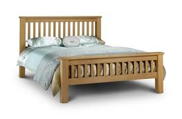 Amsterdam Oak Bed 150cm  A contemporary shaker style bed frame made from from Solid Oak and Oak Veneers. This is a robust bed that has the benefit of a fully sprung slatted sleeping base to give great comfort and extra mattress life.  Please note that the matt...
