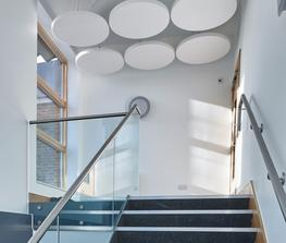 Free hanging circular panels that act as acoustic rafts fixed above workspaces. Typically these are suspended from the existing ceiling, soffit, fixtures or any suitable attachment by attractive wires  Formed from lightweight high density glass wool with a spe...