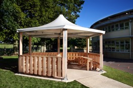 The Sheldon Hexagonal Shelter SPG311 is a more recognisable 'band stand' type external shelter, which can be used equally well for a external classroom, social or even smoking area. The Steel framework makes up the main structure of the shelter with timber clad posts and a low level barrier enclosing the shelter around 5 sides. The canopy is manufactured from stretched weather proof fabric that is available in a selection of colours to match the existing project scheme or help it blend into the landscape. The Shelter is available in two sizes (5000mm or 6000mm widths) depending on the area or amount of users that need accommodating.
