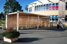 The Sheldon Shelter SPG312 was designed to provide an external waiting area protected from the elements for parents waiting for their children to finish school. The timber structure works on a standard 2500mm by 4200mm bay system and can be extended to fit the required amount of users or benching. The shelter is clad on two sides with hit or miss cladding to provide extra protection from the wind and driving rain while obscuring the view of waiting parents from the children inside. The roofing system is available in either Stucco aluminium profile sheeting or a 16mm twinwall polycarbonate finish depending of site requirements or style needs.
