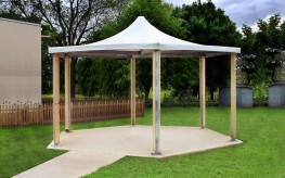 The Sheldon Hexagonal Shelter SPG315 is a 'band stand' type external shelter canopy, which can be used equally well for a external classroom, social or dining area. The steel framework makes up the main structure of the shelter with timber clad posts on all 7 legs. The canopy is manufactured from stretched weather proof fabric that is available in a selection of colours to match the existing project scheme or help it blend into the landscape. The Shelter is available in two sizes (5000mm or 6000mm widths) depending on the area or amount of users that need accommodating.