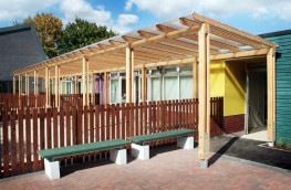 The Sheldon Shelter SPG320 is a evolution of the standard pergola type structure with the addition of a Polycarbonate roofing system for added protection from the elements. This Shelter still works on a modular bay system and can be extended to the required length to match the specific site needs. The galvanised steel feet support a timber frame and crossbeams. This shelter can be used as an entrance canopy for a single doorway or as an external teaching canopy, linking classrooms to the outside with a shelter running along the side of a building. This shelter could also be uses away from any building and provide shelter for many uses in it own right, fully customisable in length and width and material to suit the specific site requirements of the project specified.