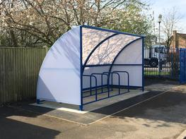 The Easydale Cycle Shelter is our most cost effective cycle shelter because of its simple design. This bike shelter has a robust steel frame with 5mm solid polycarbonate roof panels and is fitted with Sheffield cycle racks as standard to offer optimum cycle parking security. Polycarbonate side panels are available at an additional cost to provide enhanced protection from the weather.  The standard Easydale Cycle Shelter measures 4.1m x 1.7m and can hold up to 10 bikes, however it can be easily extended by 2 metre bays pre or post production to allow you to expand your cycle parking provision, as and when needed.   Because we design and install the Easydale Cycle Shelter ourselves, it can be made to BREEAM specifications if required.  All our products are fitted by our fully trained DBS checked installation teams who take great pride to ensure your bike shelter is fitted to your satisfaction, with as little disruption as possible to your site.
