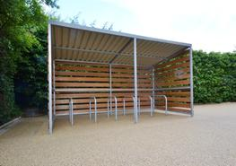The Grasmere Timber Clad Cycle Shelter is a modern, stylish bike shelter constructed from a steel frame which is covered with timber cladding on 3 sides, creating a contemporary feel to your bike storage area. It provides secure cycle parking which is ideal for many organisations including schools, colleges, leisure organisations and the hospitality sector.  The shelter's timber cladding makes it perfect for green areas such as parks or gardens as it can blend into the surroundings however it also looks good in more urban settings, creating an attractive contrast between the timber and the manmade environment. A standard Grasmere Timber Clad Cycle Shelter measures 4.1 metres x 2.05 metres and can be extended by 2 metre bays.  The shelter is covered with a very strong corrugated steel powder coated roof and comes with a 25 year life expectancy for total peace of mind. The steel frame is available galvanised, powder coated or galvanised and powder coated to any standard RAL colour. Other non standard RAL colours are available on request.  Because we design our cycle shelters in house, the Grasmere Timber Clad Cycle Shelter can be made to all BREEAM specifications. Please Contact Us for more information. All our products are fitted by our fully trained installation teams who will take great pride in ensuring that your shelter is fitted to your satisfaction.