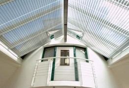 This solar shading system consists of rack arms onto which either aluminium or timber slats are securely held. The slats can then be adjusted to attenuate the light entering the space. Operation is usually by electric motor but gearbox operation is available systems fitted at low level. The Astralux system 6000 is ideal for large areas of glazing, especially roof and sloping glazing and the system can be manufactured to fit shaped applications.