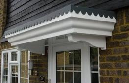 A flat-topped lead look canopy with scalloped edge feature over a smooth white fascia incorporating period detailing.  A simulated lead effect top with scalloped edge over a smooth period fascia means that this over door canopy will enhance any door opening...