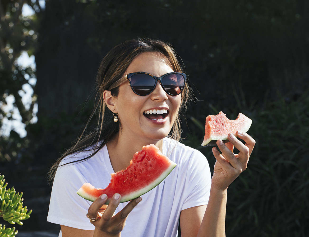 Woman really enjoying watermelon wearing sunglasses