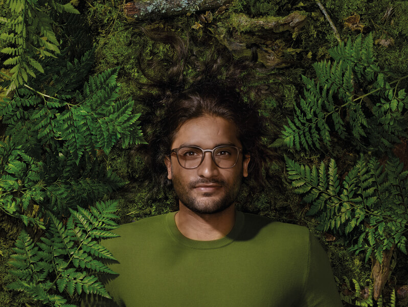 Man wearing Reframe glasses and lying in green leaves