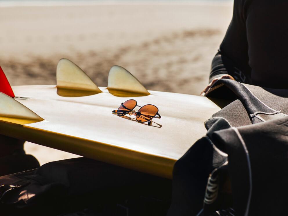 HACKETT SUN RX 01 resting on surfboard