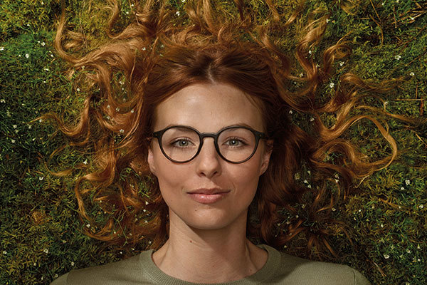 Lady lying in grass wearing rounded glasses