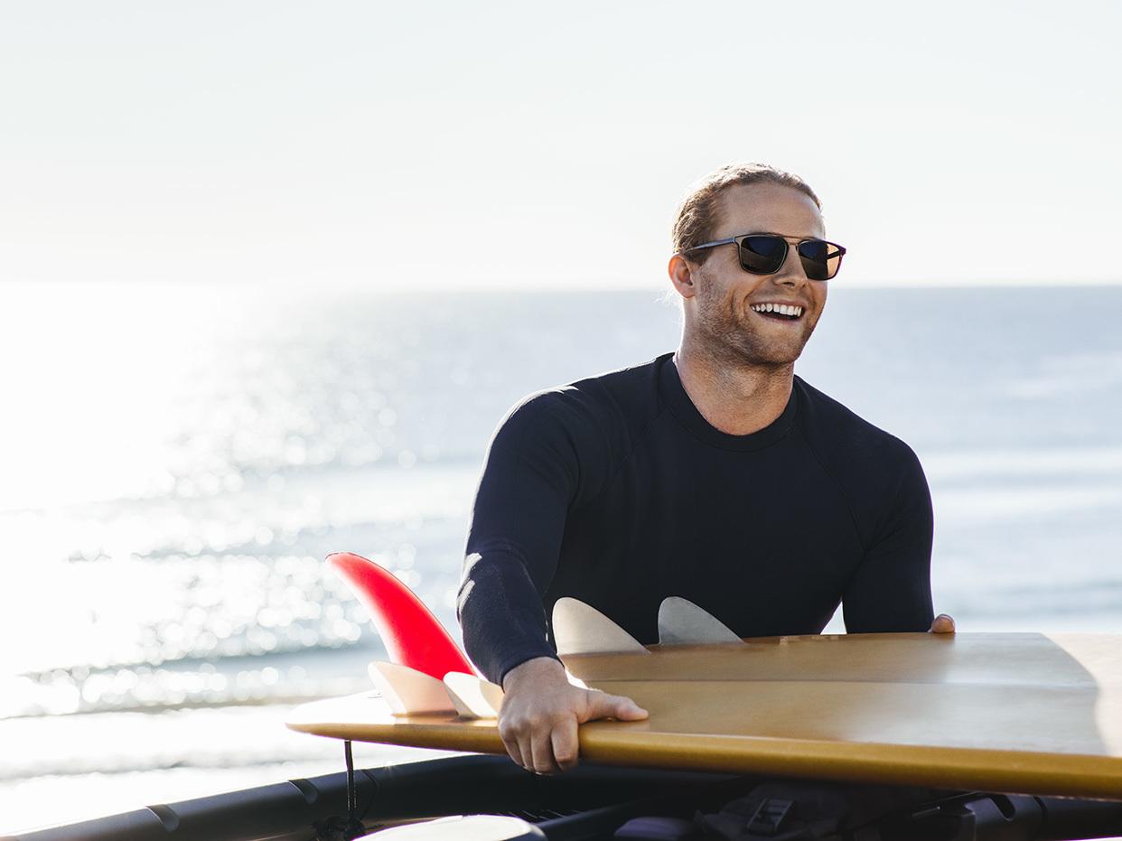 Man on surfboard wearing sunglasses