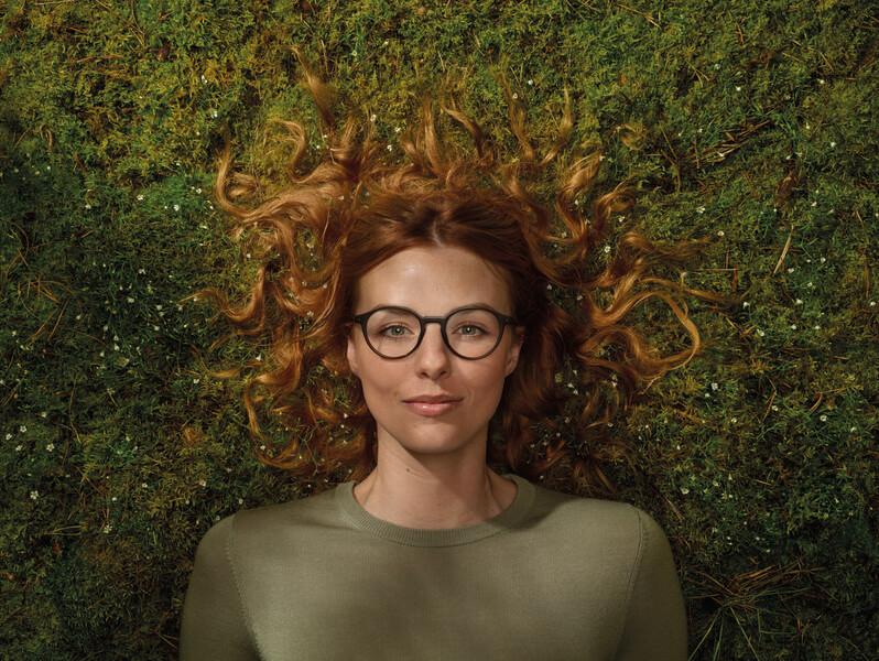Woman wearing ReWear glasses in Mossy ground.