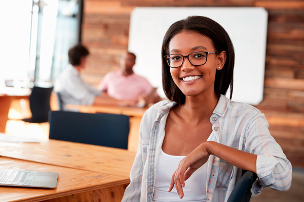 Woman at work wearing black glasses, sat at a table with a laptop