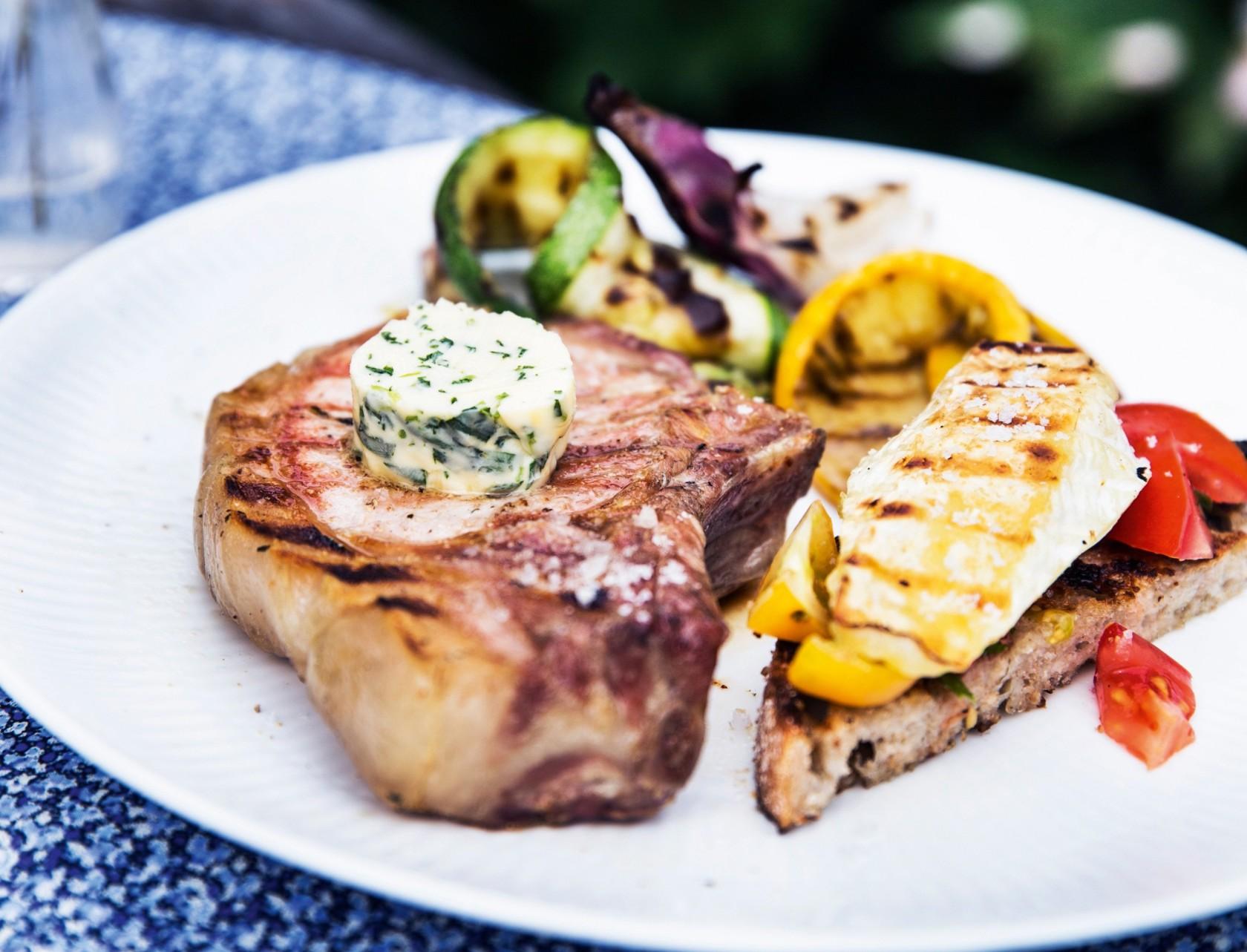 Svinekoteletter med estragonsmør, grillede grøntsager og brød med brie.