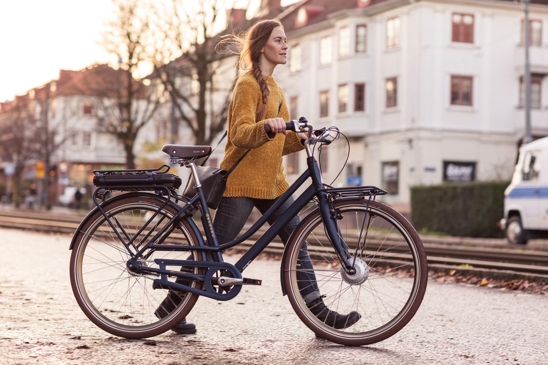 Kvinna som går med en Commuter Elcykel från Monark