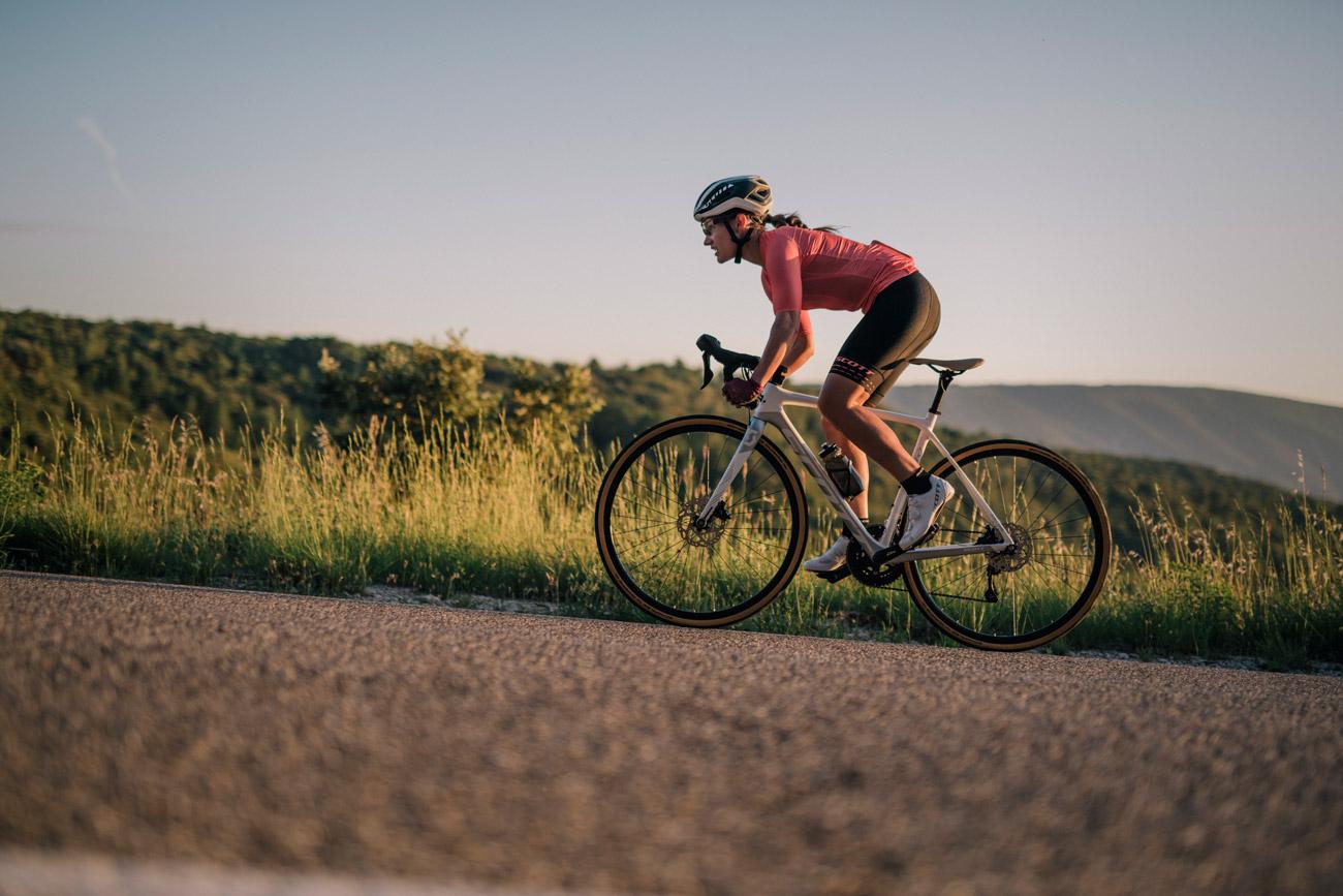Kvinna som cyklar i uppförsbacke på en racercykel