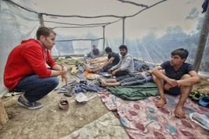 A Samaritan's Purse staff member (in red) listens as young men share their journey from Iraq to Europe.