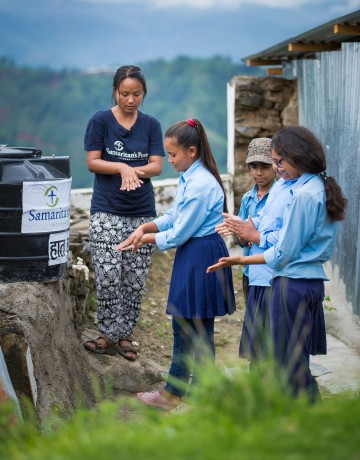 Staff member Sujana Lama teaches hand-washing techniques to schoolchildren.