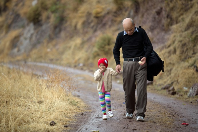 A man walks across Lesbos Island, Greece, with his granddaughter. Along the way, they received bananas and water from Samaritan's Purse.