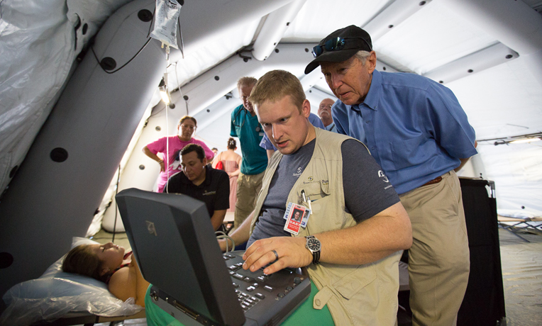 Dr. Richard Furman (background) observes as Dr. Elliott Tenpenny conducts an ultrasound at our emergency field hospital in Ecuador.