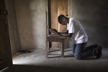 Harrison prays inside his home in Lofa County, Liberia. His house is located a short walk from the Ebola Treatment Unit.