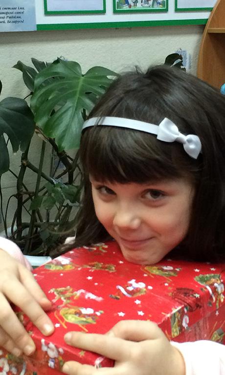 Little girl hugging red shoebox
