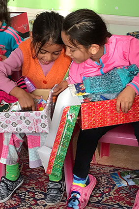 Girls exploring shoebox gifts
