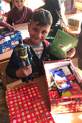 Smiling boy holding batman toy