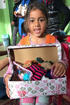 Girl holding shoebox gift open