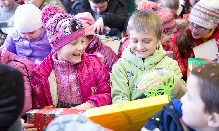 Boy and girl smile as they explore their shoebox gifts