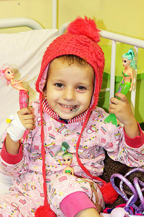Smiling child in hospital with hat and toy mermaids