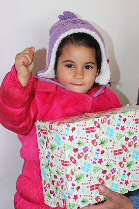 Girl in pink coat with shoebox gift