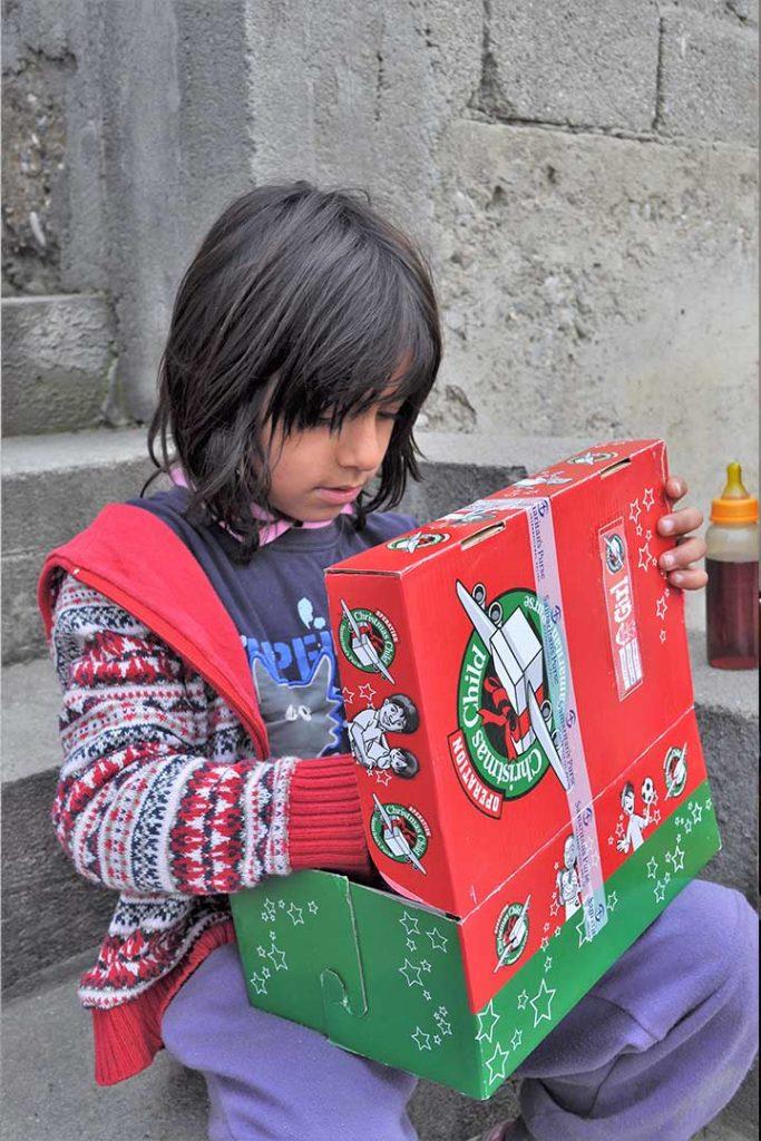 Child explores shoebox gift