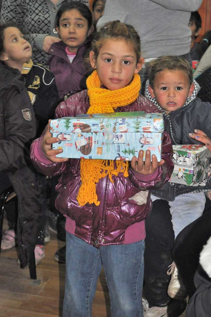 Girl holding wrapped shoebox gift in Macedonia