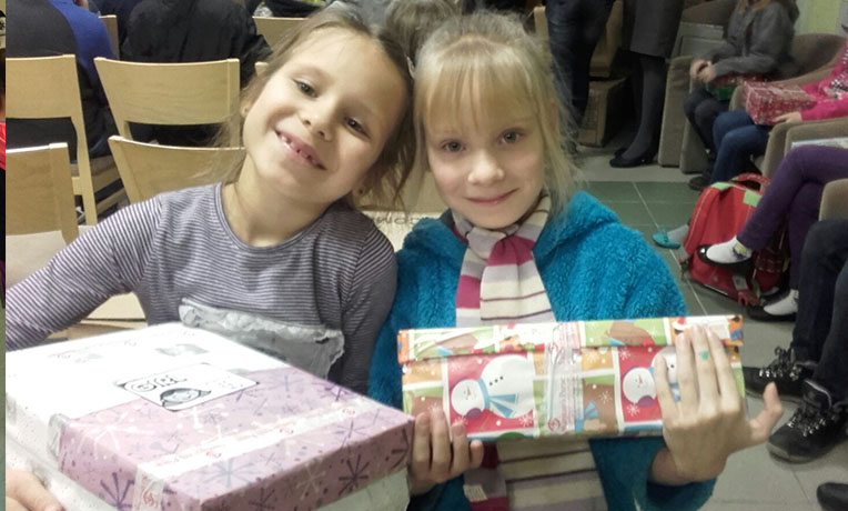 Girls smile with shoebox gifts