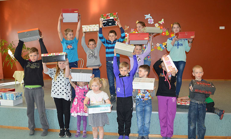 Group hold up their shoeboxes in Latvia