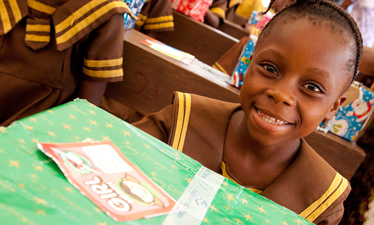 Smiling school child with green shoebox gift